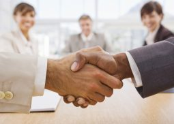 Portrait of happy businesspeople shaking hands together with colleges in background